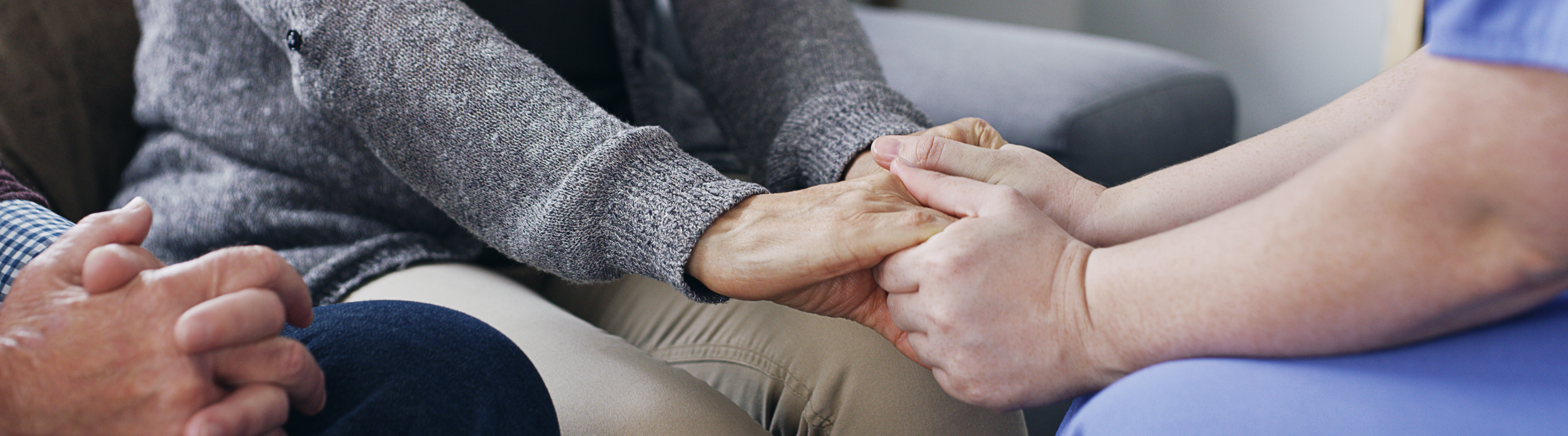 Close up image of two people holding hands